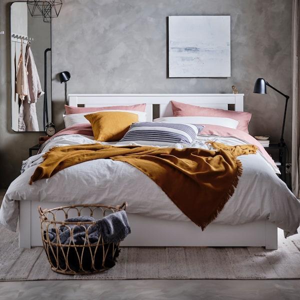 ห้องนอนที่มีเตียง SONGESAND/ซองเงซันด์ พร้อมเครื่องนอนลายทาง BERGPALM/แบริพาล์ม ผ้าคลุมสีเหลืองเข้ม และปลอกหมอน PUDERVIVA/พูเดอร์วีว่า สีชมพูเข้ม