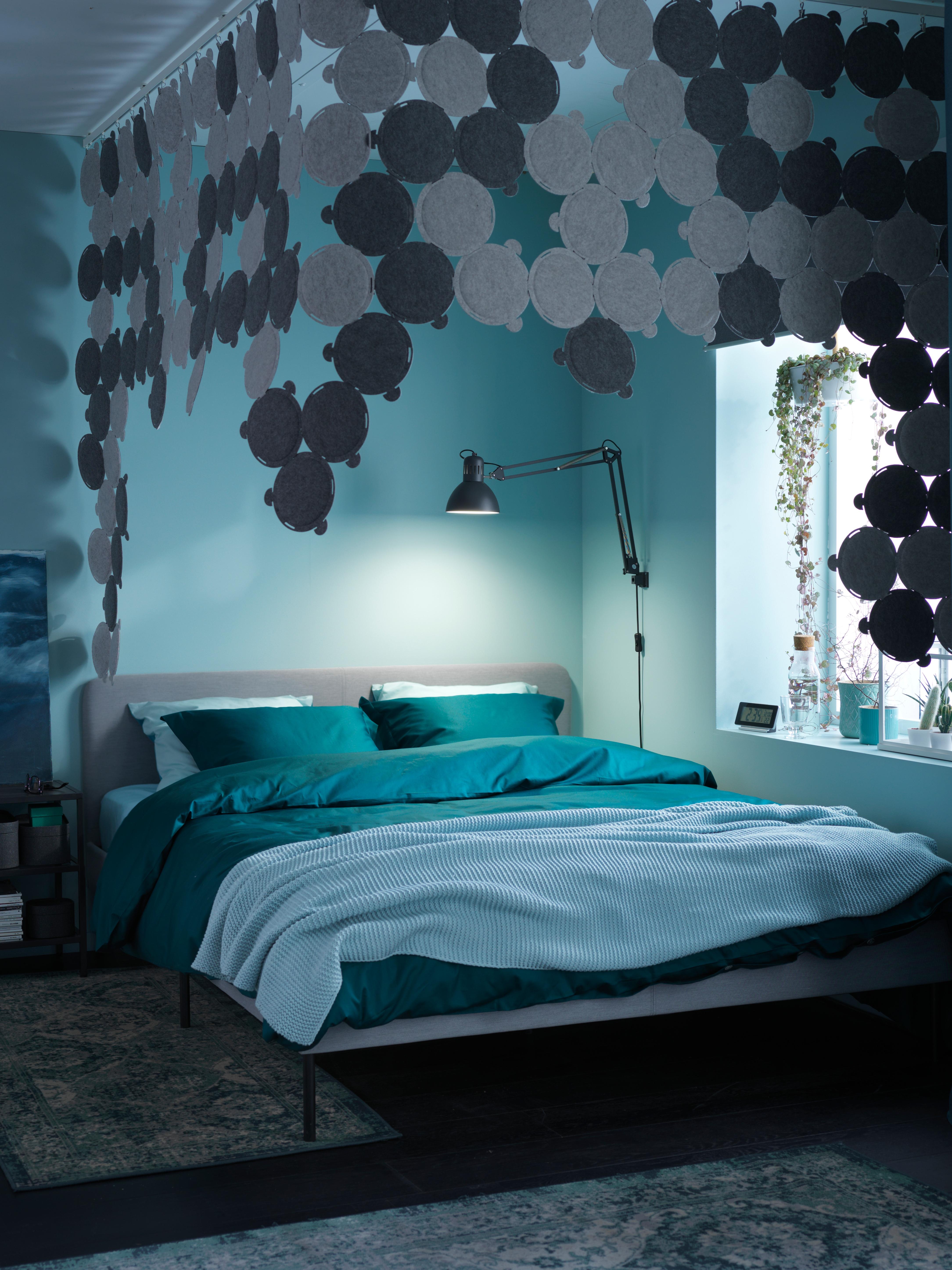 読書ランプと吸音パネルがつり下げられた部屋にあるSLATTUM/スラットゥム 布張りベッドフレームと寝具