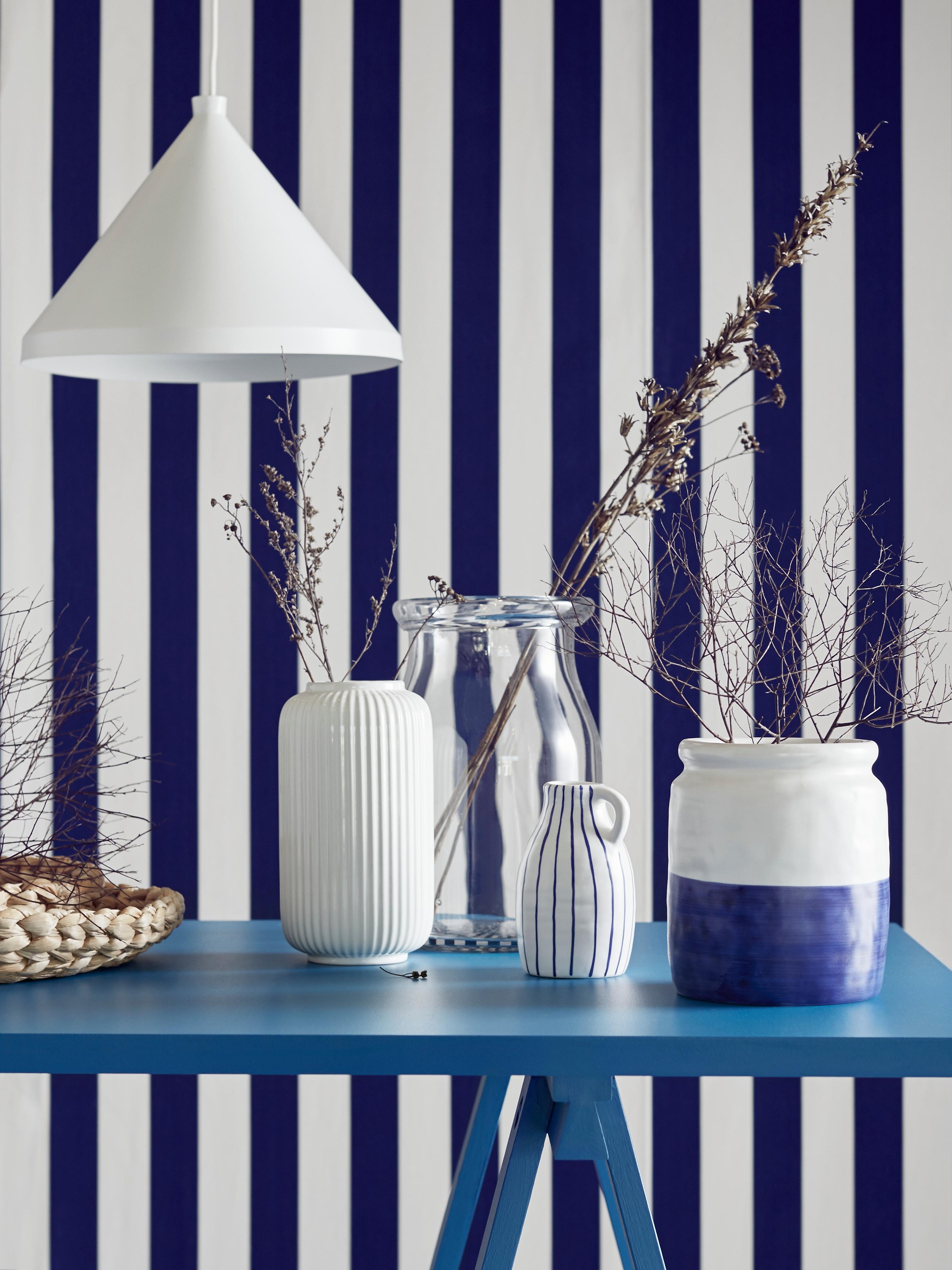 Tre vasi in ceramica bianchi e blu su un tavolo blu, con carta da parati a righe bianche e blu sullo sfondo.