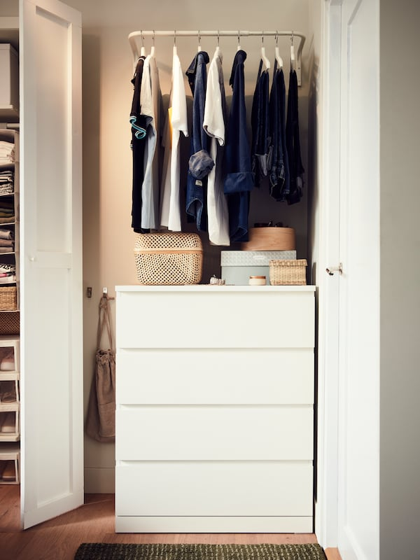 A white chest of drawers in a small nook with boxes on top. A clothes bar hangs above it with shirts and jeans on hangers.