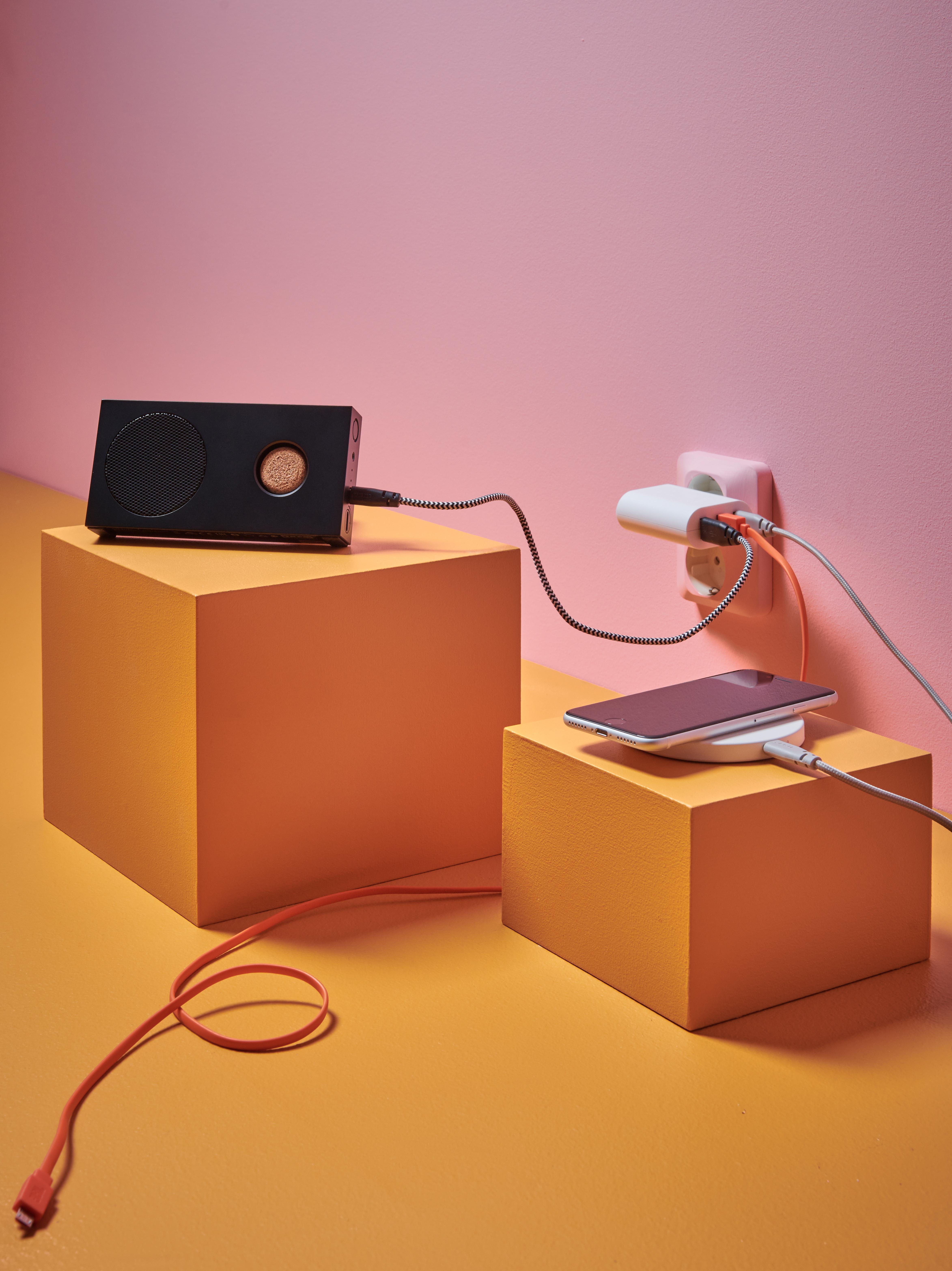 Uno spazio rosa/arancione con espositori su cui sono appoggiati una cassa e un caricabatterie Bluetooth, collegati a una presa di corrente tramite cavi USB.