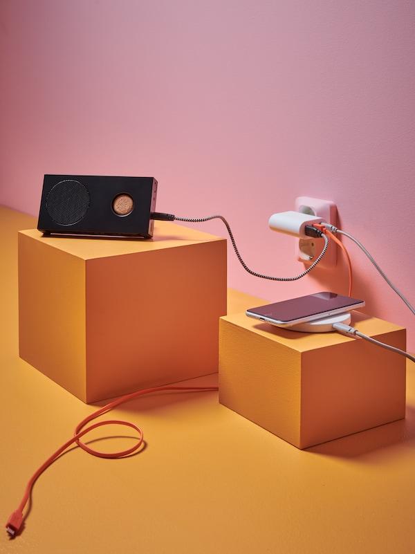 Na narančastom podu ispred zida roza boje nalaze se Bluetooth zvučnik i punjač za mobitel spojeni u struju USB kablom.