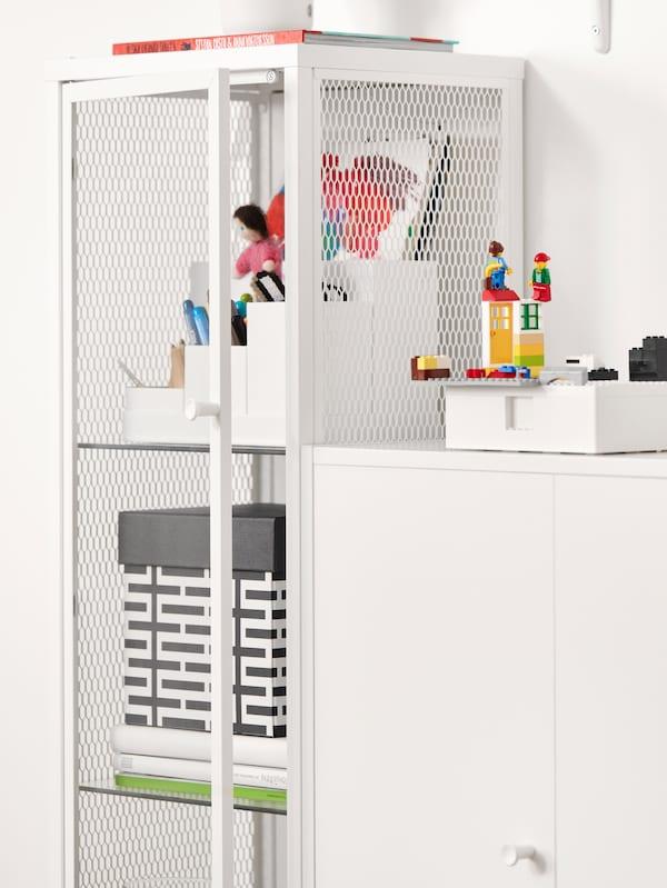 Et hvidt vitrineskab med bøger, en kasse og hvid skrivebordsopbevaring med hobbymaterialer.