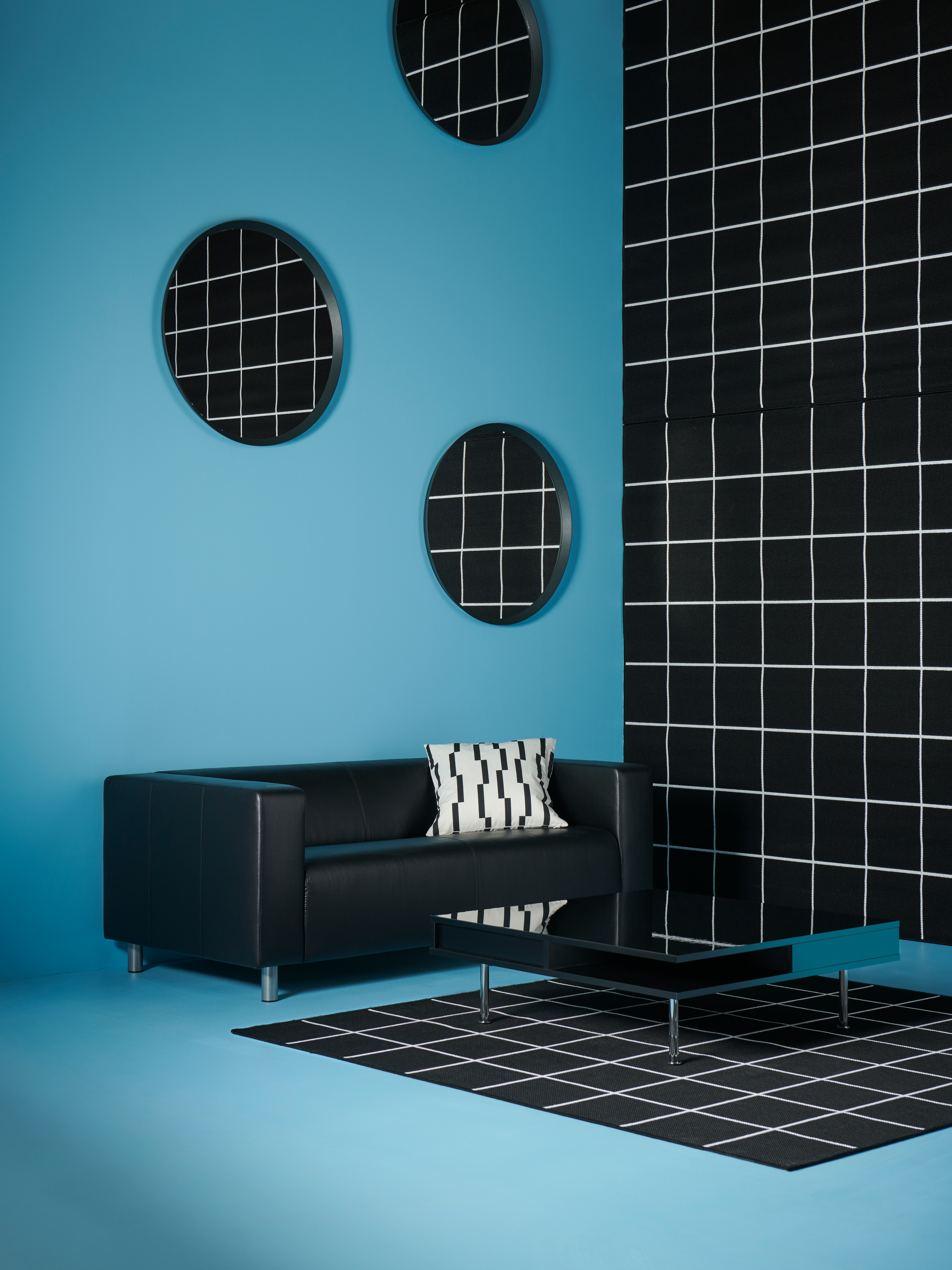 Modern interior with black sofa, black and glossy coffee table, flat woven rug, mirror and cushion cover.