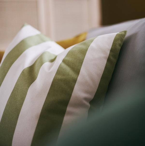 Réalisée dans un tissu 100% coton, la housse de coussin HILDAMARIA est rayée de vert et d'écru.
