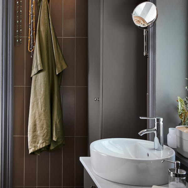 A bathroom with GODMORGON cabinets in dark-grey, white sink and brown tiles. A green robe and necklaces hang from hooks.