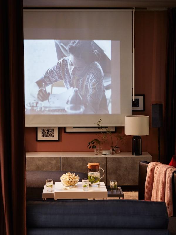 En mørk stue, hvor en film vises på et mørklægningsrullegardin, et tv-bord med låger og popcorn.