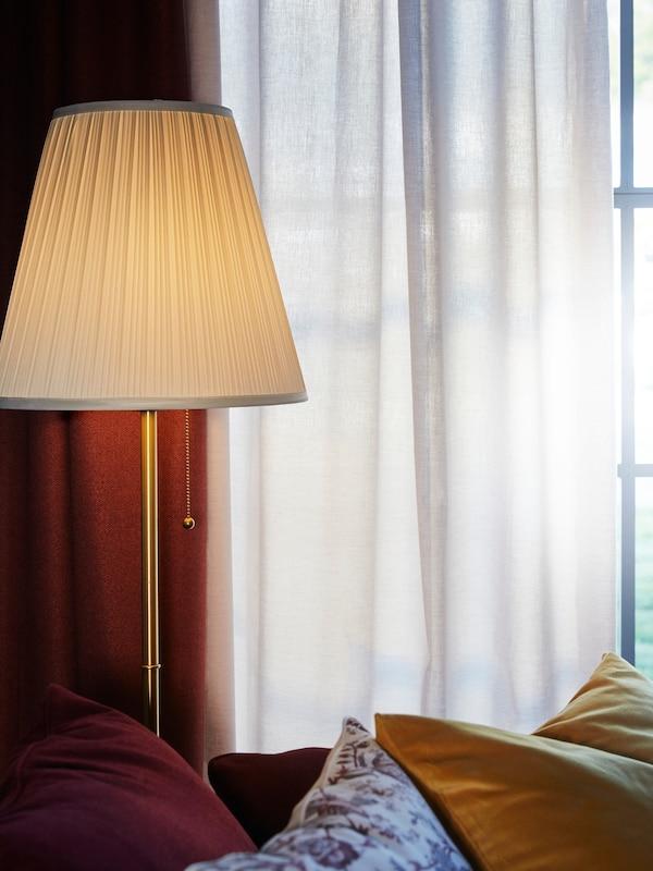 스탠드를 켜놓은 커튼을 친 창가의 모습
