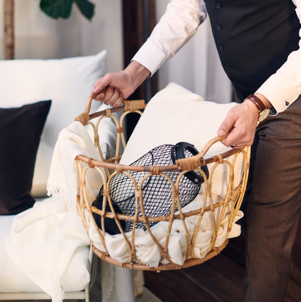 A pair of hands carrying a SNIDAD rattan basket with a TOPPIG lantern for block candle, a throw and a cushion in it.