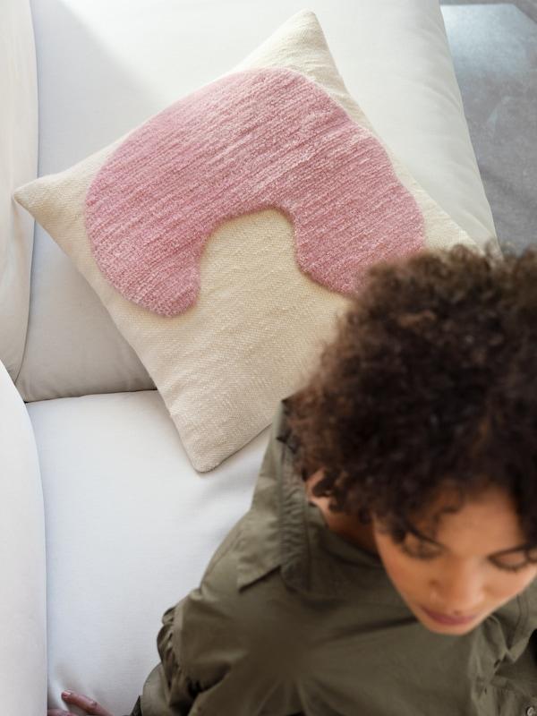 Женщина сидит перед подушкой ЛОКАЛЬТ ручной работы. Белая подушка украшена розовыми ворсовыми вставками.
