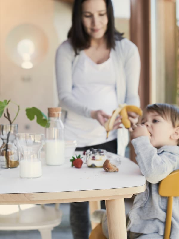 A woman with brown hair feeds a child a banana. The child is sitting at a white and pale wood kitchen table.