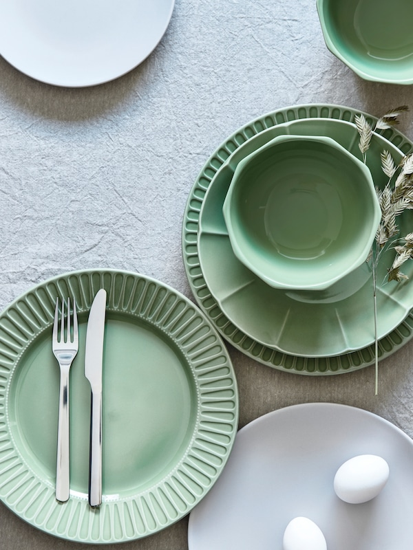 A table setting with STRIMMIG flower-inspired tableware in green. There is also a white plate with two eggs on the table.