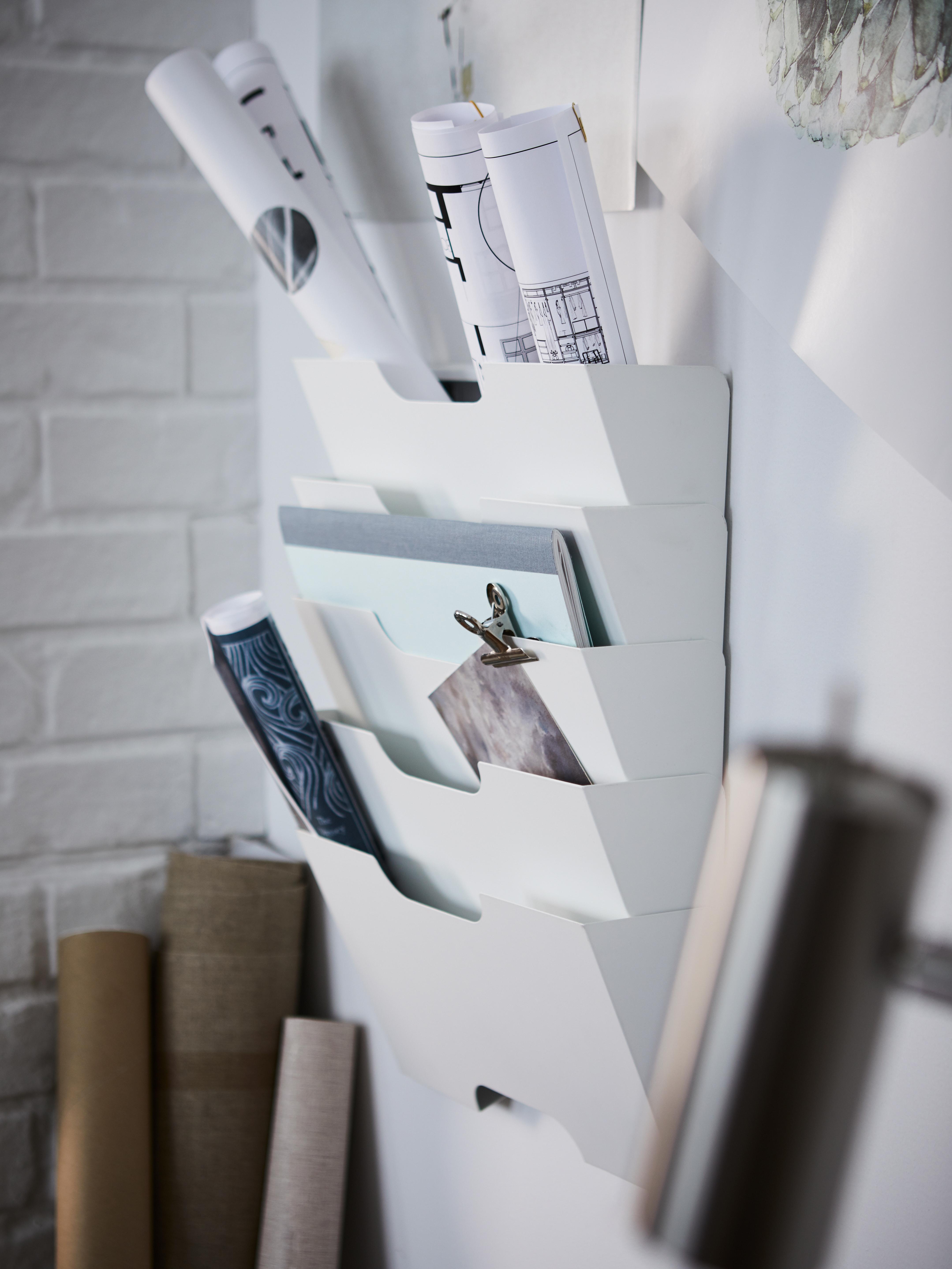 Un range-revues mural blanc KVISSLE, plein de documents et dessins. Des rouleaux de carton sont appuyés contre le mur.