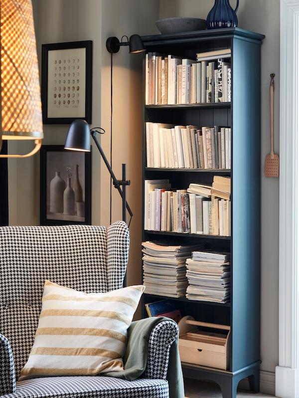 Un colț de lectură confortabil, cu o veioză SKURUP, un lampadar, un scaun cu brațe și o bibliotecă în combinația de culori albastru-verde închis.