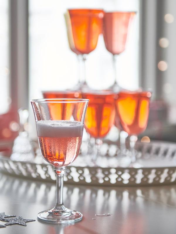 Dans une salle à manger lumineuse, plan rapproché de verres de rosé empilés sur un plateau.
