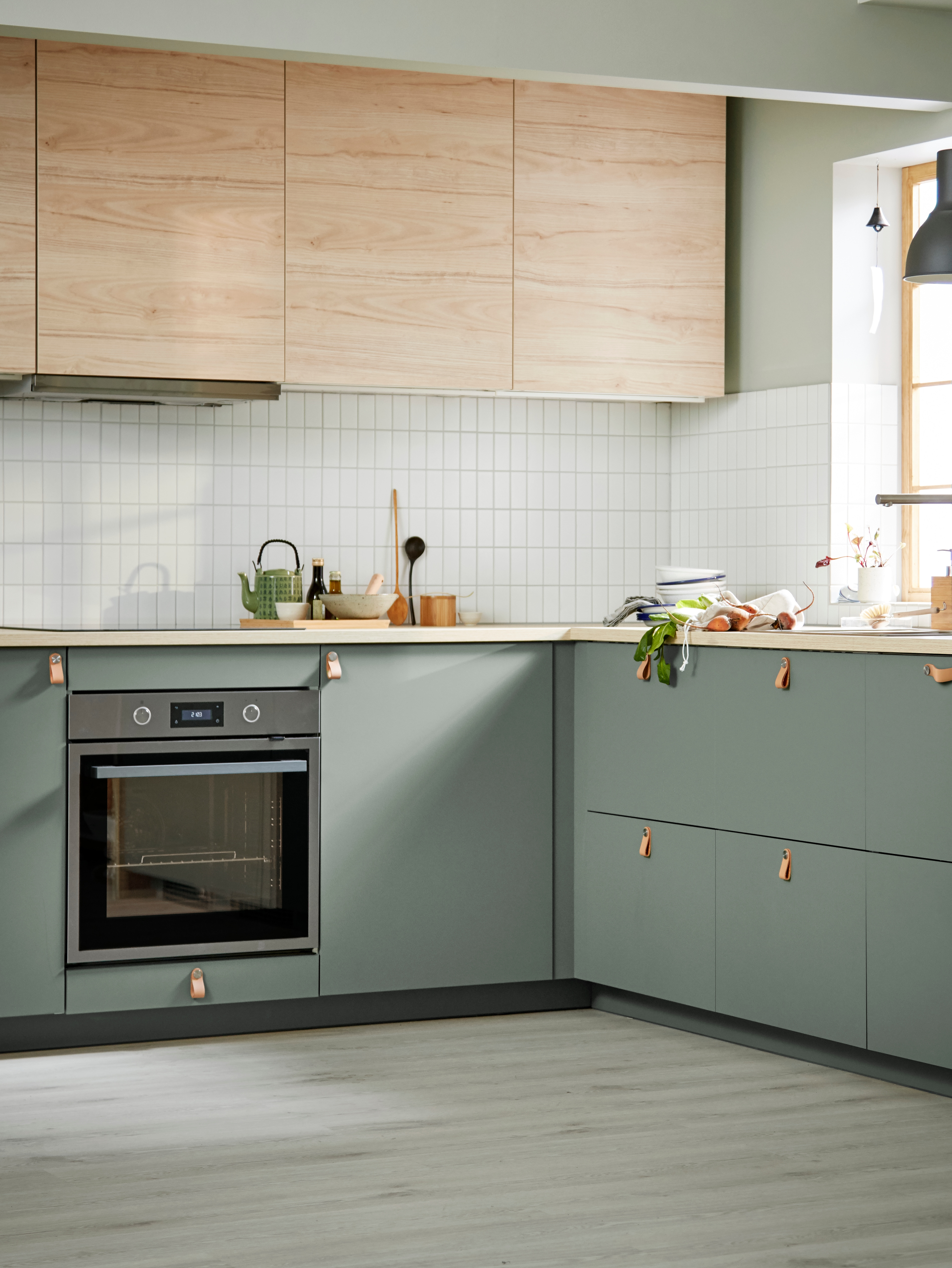 An airy kitchen has a mix of ASKERSUND light ash effect doors on wall cabinets and grey-green fronts on base cabinets.