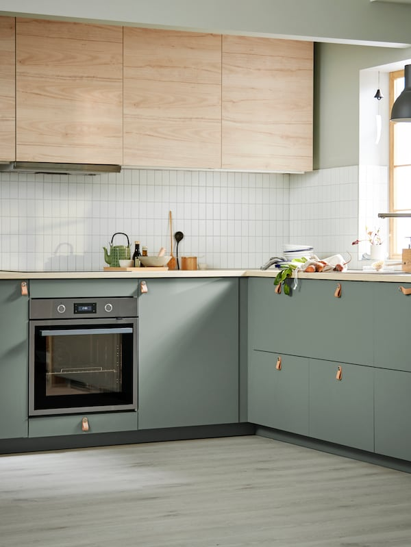 A green BODARP kitchen with wooden accent doors.