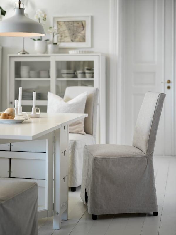 Biely sklápací stôl NORDEN sbéžovými stoličkami BERGMUND. Pri stene za stolom stojí vitrína HAVSTA.