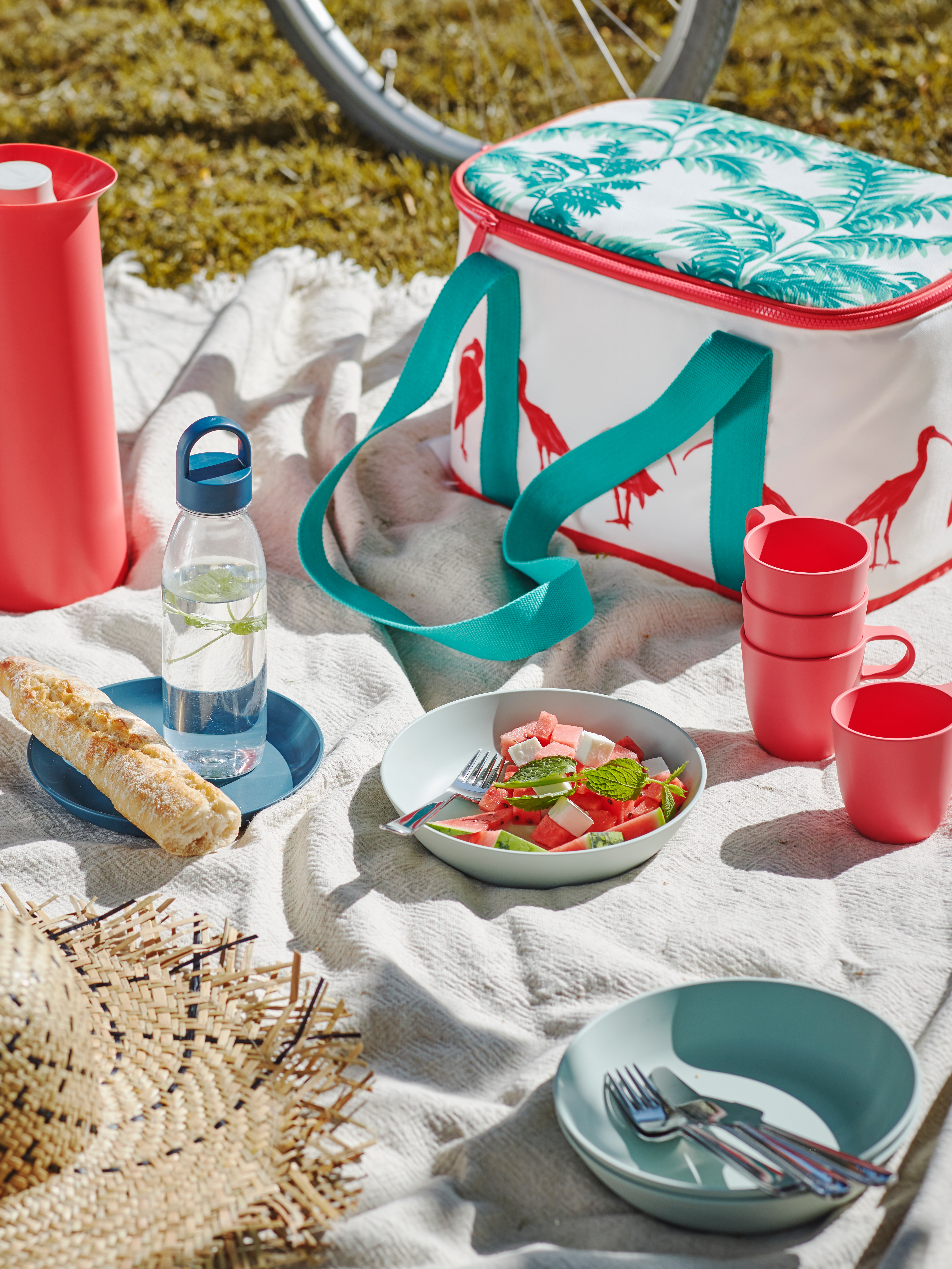 Plates with salad and bread are on a throw on some grass, by a stack of light red TALRIKA mugs, a hat and a cooler bag.