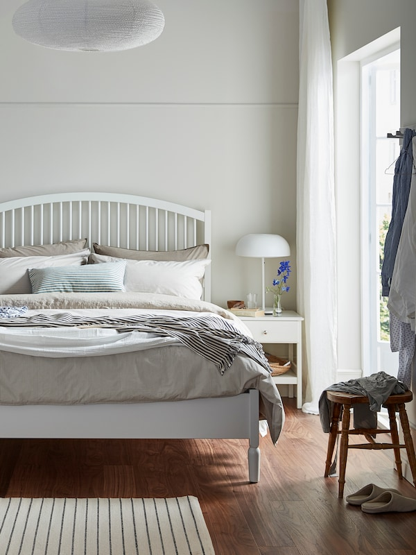Open bedroom with white bedframe and neutral accessories and linen