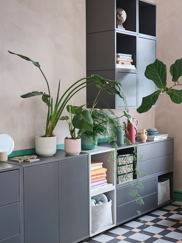 Sleek grey and white cabinets with shelves, drawers and doors. Green plants are displayed on top of the lower cabinets.