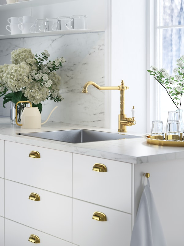 A kitchen with EKBACKEN white marble effect/laminate worktop, white fronts and brass-coloured tap and handles.