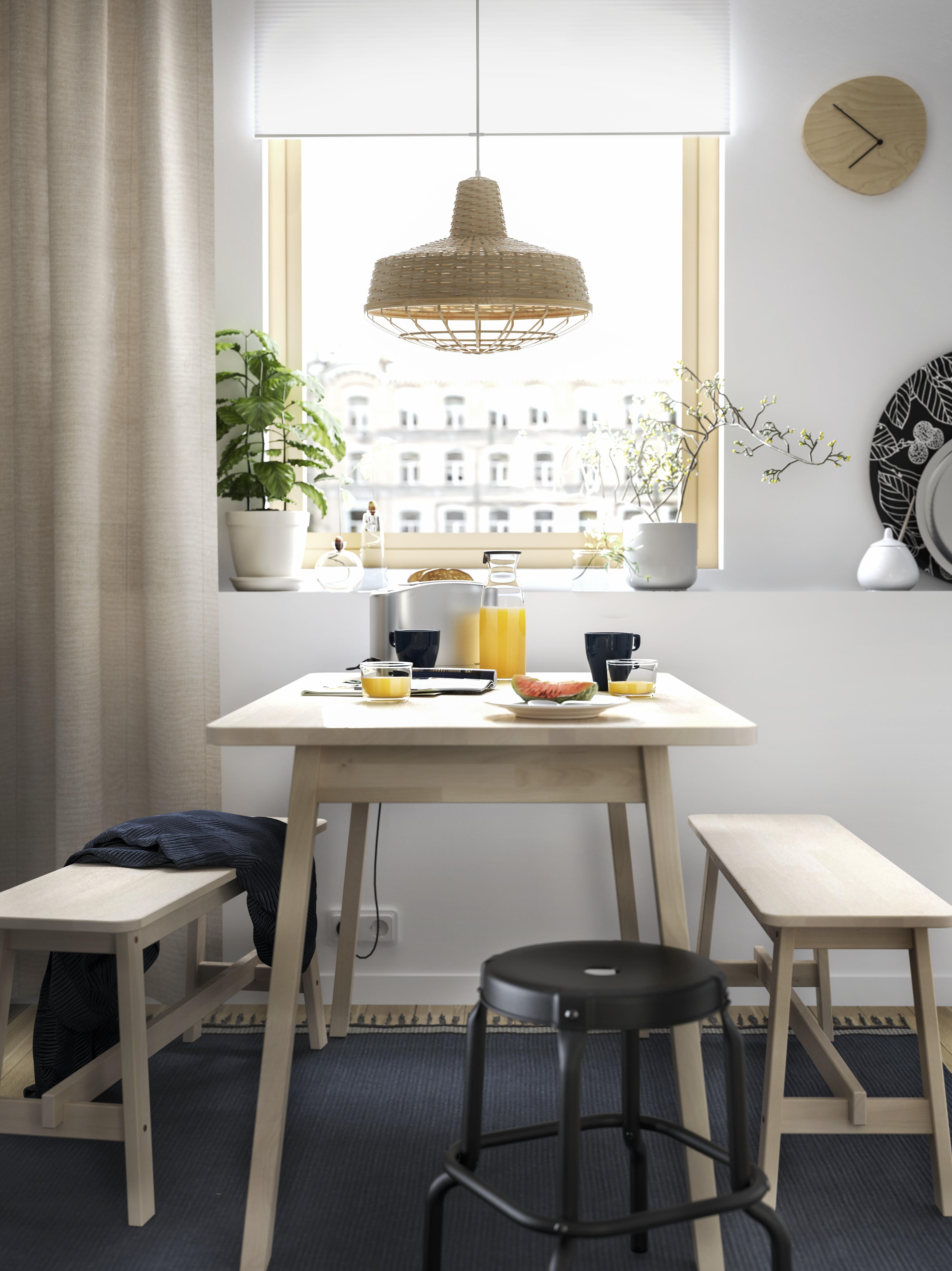 Un posto per mangiare vicino ad una finestra con un tavolo da pranzo NORRÅKER in betulla, due panche, uno sgabello nero e un tappeto blu.
