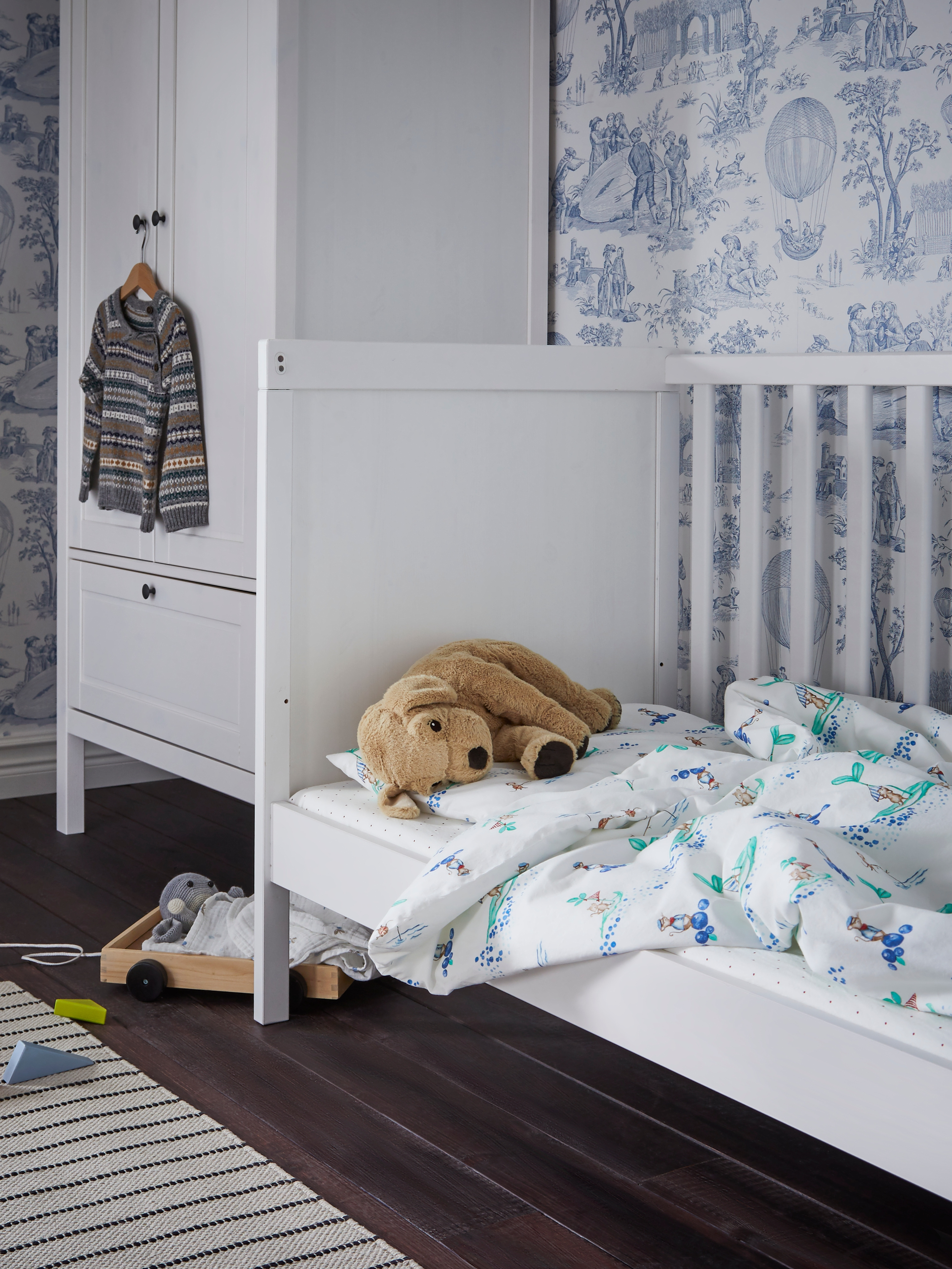 A white SUNDVIK cot with a side removed for a three-walled bed with blue and white bedding and a soft toy do by a wardrobe.