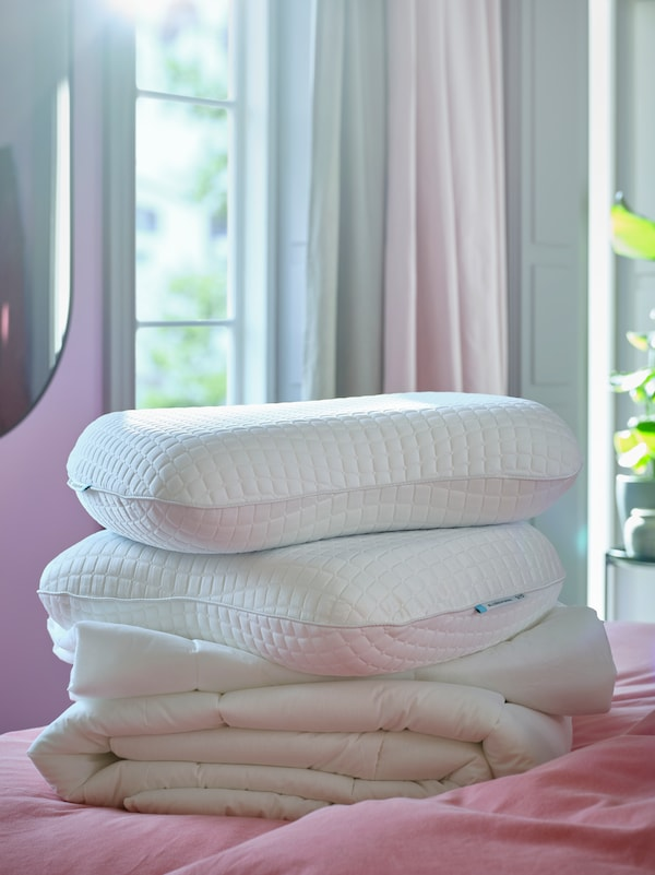Two KLUBBSPORRE ergonomic pillows sit on a duvet on a bed in a bedroom with a window and curtains in the background.