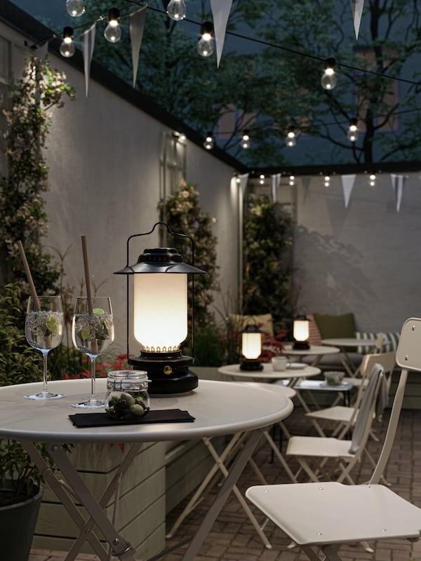 Caffè all'aperto in ambientazione serale, con lanterne nere su tavoli da esterno beige, sedie pieghevoli, illuminazioni decorative e ghirlande di bandierine.