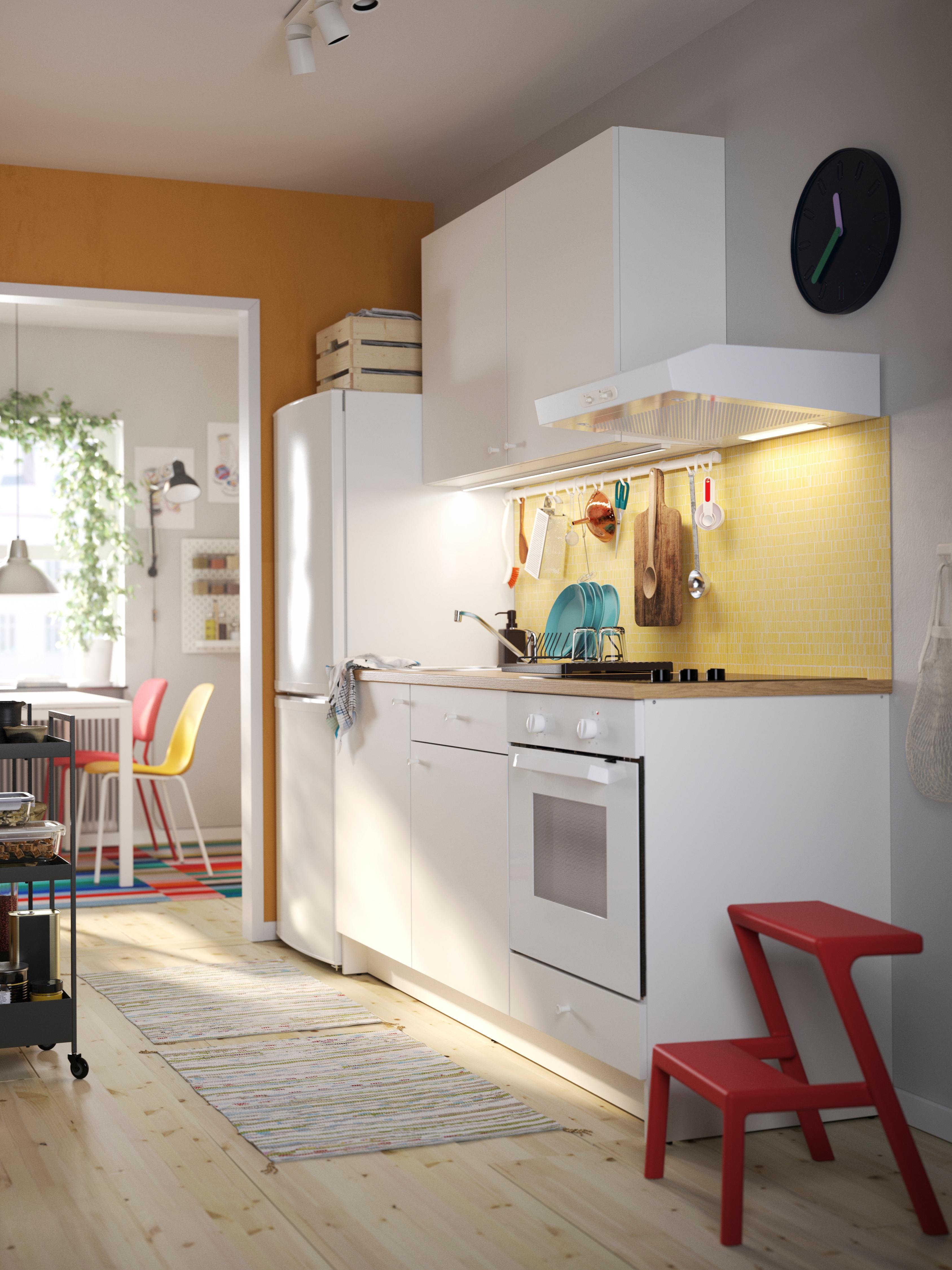 Weiße KNOXHULT Schränke mit Türen und Schubladen in einer Küche mit zwei Teppichen und einem roten Tritthocker auf einem Holzboden.