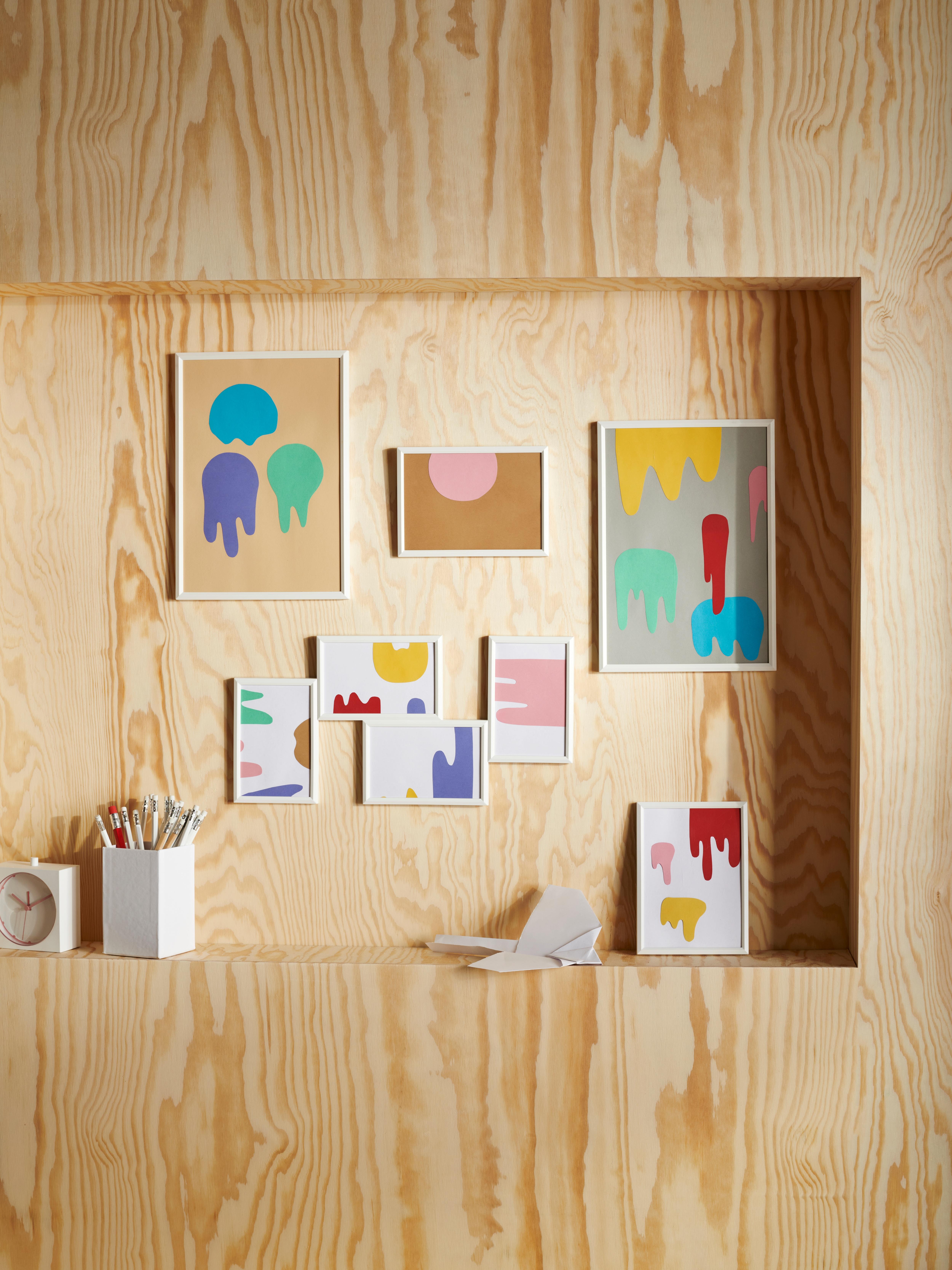 An einer hellen Sperrholzwand sind weisse Bilderrahmen in verschiedenen Grössen aufgehängt.