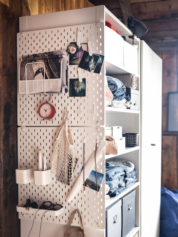 Two white, SKÅDIS pegboards with various SKÅDIS accessories hang from the side of a white wardrobe using SKÅDIS connectors.