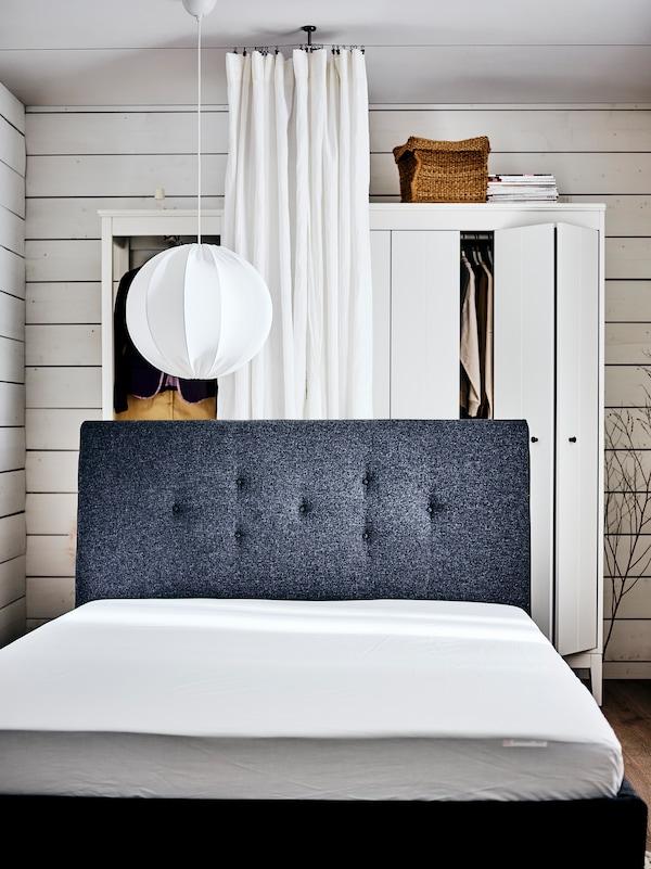 Ein weisses Schlafzimmer mit einem IDANÄS Polsterbett ohne Bettwäsche vor zwei weissen IDANÄS Kleiderschränken und einer Gardine.