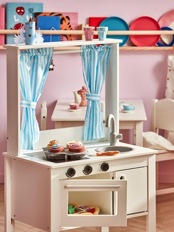 儿童房里摆放一个SPISIG 斯皮西格 玩具厨房,挂着挂帘,台面和里面都放着各式各样的玩具食品。