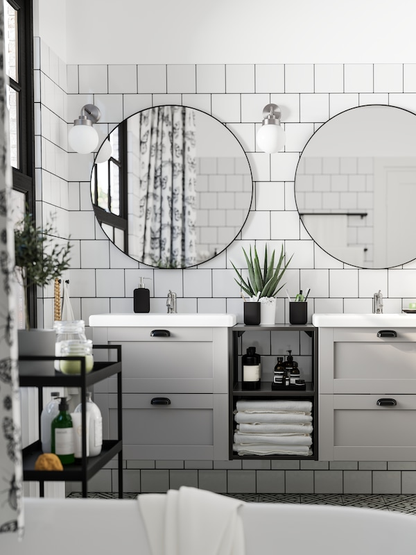 Two round LINDBYN mirrors side by side on a white tiled wall above two white wash-stands, each with 2 grey drawers.