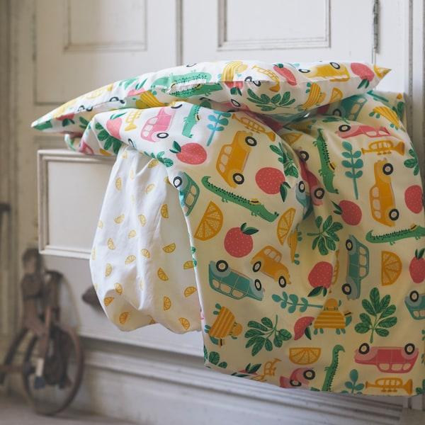 Xogo de roupa de cama de algodón RÖRANDE multicolor de 3 pezas para un berce cae dende un caixón aberto dun armario.