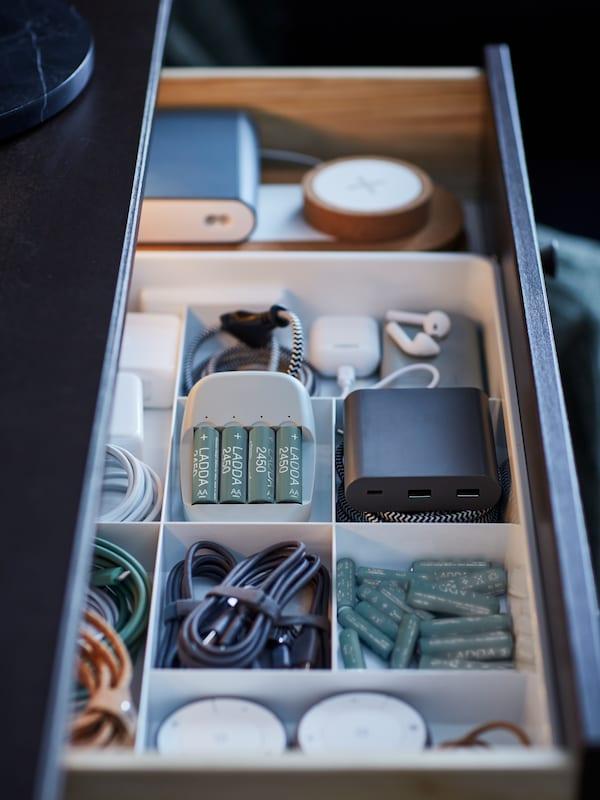 Un tiroir ouvert révélant un rangement à huitcompartiments KUGGIS blanc rempli de piles, de chargeurs et de câbles.