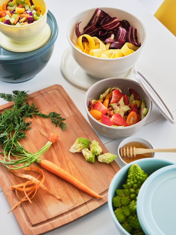 Chopped-up vegetables and fruits on a chopping board and divided into multiple mixed-colour GARNITYREN lidded bowls.