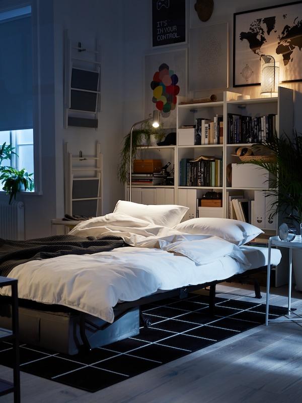 2-pers. sovesofa slået ud som en seng, et hvidt sengesæt, hvide reoler og kunst på væggene.