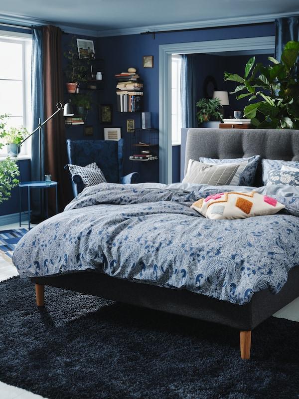 Dormitorio con diferentes tons de azul e moitos coxíns, un deles cunha funda BRUNSTARR en cor natural/multicolor.