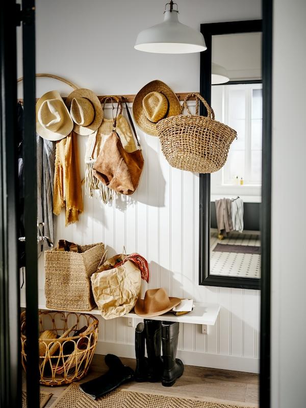 Un hall d'entrée blanc avec soubassement en lambris de bois, avec des chapeaux en paille et des paniers accrochés sur une rangée de boutons. Un banc est installé en dessous et un miroir, à côté.