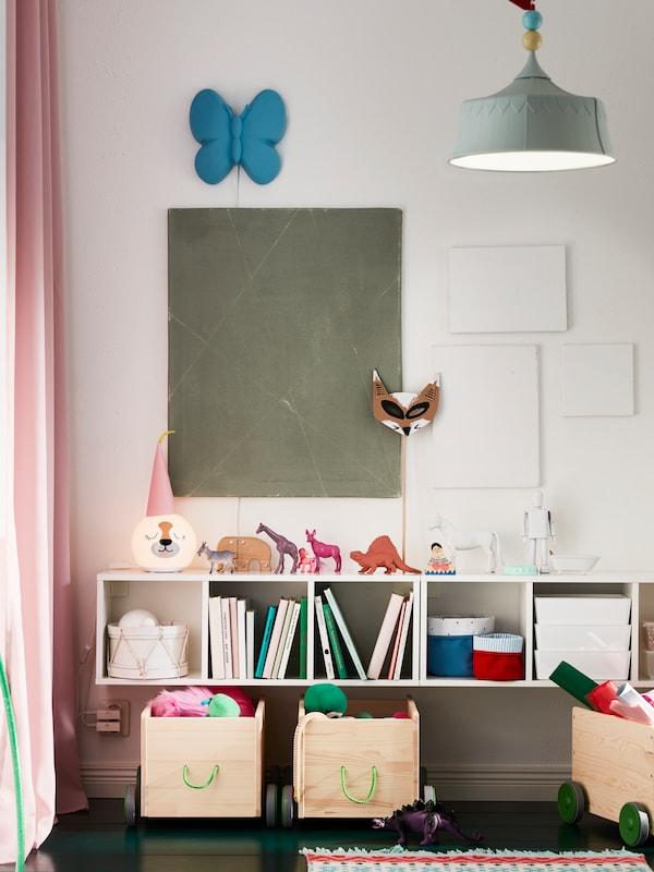 O etajeră albă, montată pe perete. Cutii, cărți, coșuri și o lampă de birou sunt așezate pe rafturi și pe partea de sus.