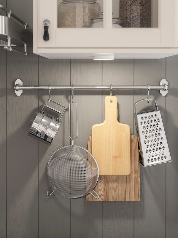 A close-up of utensils such as a grater and small cutting boards hanging from an IKEA FINTORP stainless steel rail.