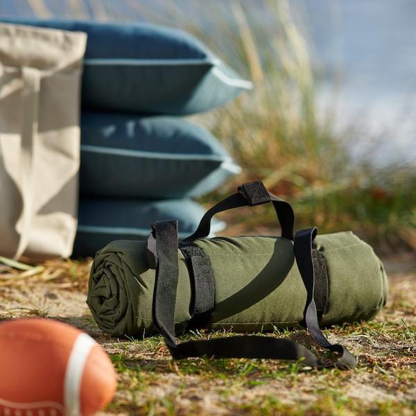 En grön väska syns på gräset vid vatten.