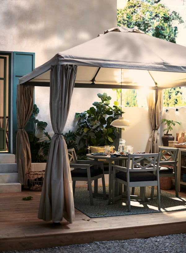 Une table à manger d'extérieur BONDHOLMEN et des chaises grises où quatre personnes peuvent profiter d'un souper en plein air sur la terrasse, sous une tonnelle en tissu.