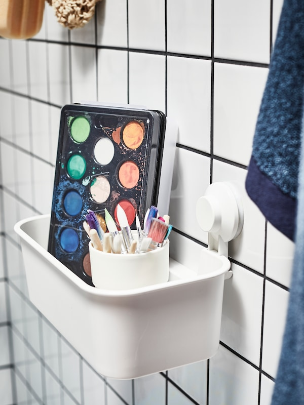 MÅLA watercolour box and a cup of brushes in a white, TISKEN basket with suction cup attached to a white-tiled wall.