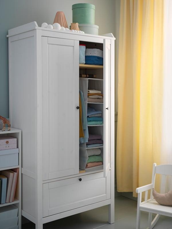 Lângă o fereastră cu perdele galbene se află un balansoar și un dulap de haine. Una dintre ușile dulapului este deschisă, lăsând să se vadă hainele împăturite.