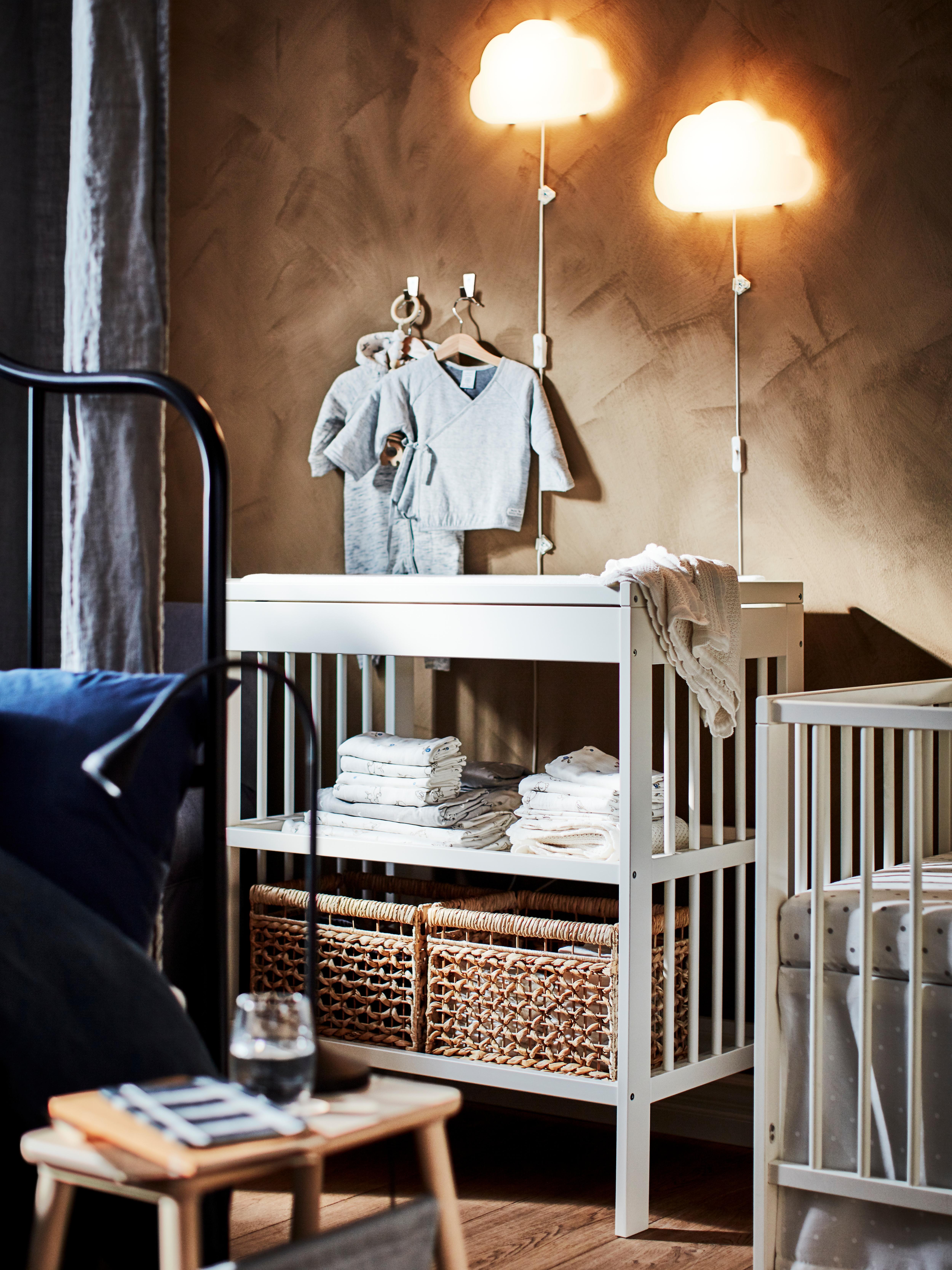 GULLIVER puslebord i et soveværelse med kurve og tekstiler på hylderne. Der er to UPPLYST LED-lamper på væggen.