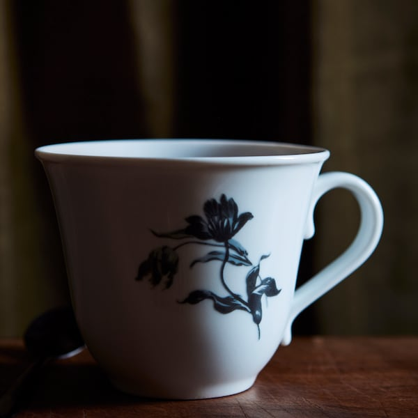 A white UPPLAGA cup with a blue flower pattern on it placed on a dark brown wooden table.